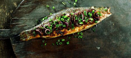 garnished: High Angle View of Whole Roasted Fish Garnished with Red and Green Onions on Rustic Wooden Cutting Board
