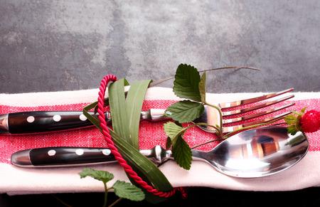 servilleta de papel: Cubierto decorativo atado con hojas frescas y cordón rojo alrededor de un juego rojo servilleta, tenedor y cuchara en una mesa oscura con copyspace, vista de cerca Foto de archivo