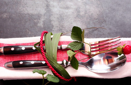 serviette: Decorative place setting tied with fresh leaves and red cord around a matching red serviette, fork and spoon on a dark table top with copyspace, close up view
