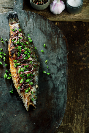 view on sea: High Angle View of Whole Roasted Fish Garnished with Green Onions Resting on Rustic Wooden Cutting Board with Copy Space