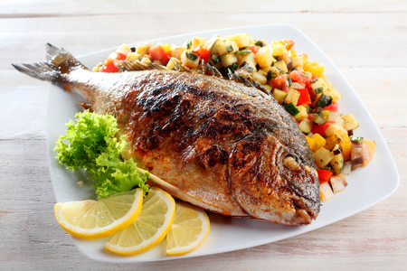 dorade: High Angle View of Roasted or Grilled Whole Fish Garnished with Lettuce and Lemon Wedges Served on Bed of Fresh Chopped Salsa and Presented on White Dish on Rustic Wooden Table Stock Photo