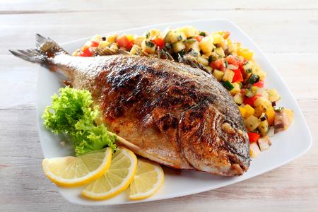 plato de pescado: Ángulo de visión de alta de asado a la parrilla o pescado entero con guarnición de lechuga y Cuñas de limón Servido en cama de fresco picado Salsa y presentado en un plato blanco sobre mesa de madera rústica
