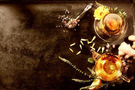 コピー スペースを持つ黒メタル プレートにみじん切りにしたインド紅茶概念。おいしい生姜岩砂糖の花と紅茶とお茶のポットと紅茶のカップとペパ