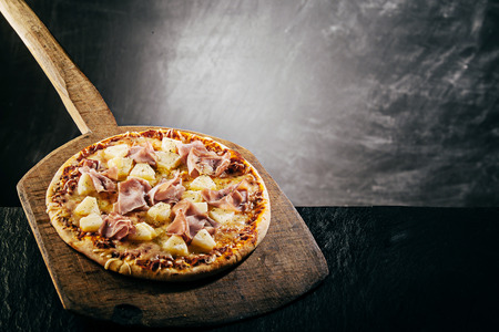 long handled: Steaming hot flame grilled Italian pizza in a pizzeria topped with ham and pineapple on melted mozzarella served on a long handled wooden board, copyspace behind