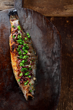 garnished: High Angle View of Whole Roasted Fish Garnished with Green Onions Resting on Rustic Wooden Cutting Board with Copy Space