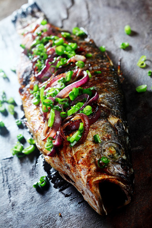 dace: Close Up of Whole Roasted Fish Garnished with Red and Green Onions on Rustic Wooden Cutting Board Stock Photo