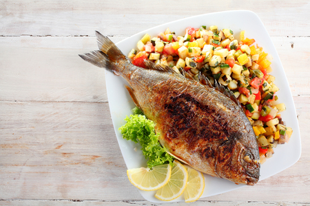 dorade: High Angle View of Roasted or Grilled Whole Fish Garnished with Lettuce and Lemon Wedges Served on Bed of Fresh Chopped Salsa and Presented on White Dish on Rustic Wooden Table with Copy Space