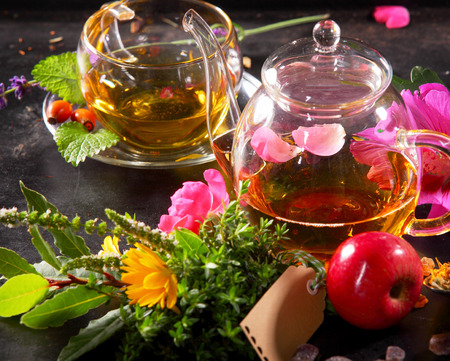 flowering: Tea pot and Tea cup on black background with fruity rose flowers and herbs tea sorts with an empty tag Stock Photo