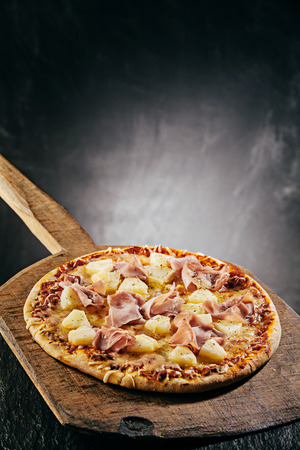 Delicious Hawaiian Italian pizza topped with tropical pineapple and ham on melted mozzarella cheese served steaming hot in a restaurant or pizzeria Stock Photo