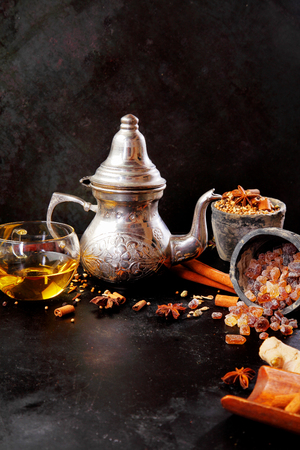 stick of cinnamon: Silver teapot and cup of hot spicy tea with associated ingredients including stick cinnamon, star anise and caramelized sugar crystals on black with copyspace Stock Photo