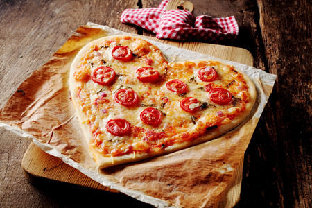 Baked heart-shaped homemade pizza topped with mozzarella and tomato slices, on parchment paper on a cutting board near a checkered red and white kitchen towel, on a rustic table, high-angle close-up Stockfoto
