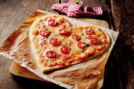 romance: Pizza caseira em forma de coração cozido coberto com mussarela e tomate fatias, no papel de pergaminho em uma placa de corte perto de uma toalha de cozinha checkered vermelho e branco, em uma tabela rústica, de alto ângulo close-up