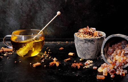 stick of cinnamon: Delicious cup of aromatic spiced tea made with stick cinnamon and star anise and sweetened with a crystallised sugar stick for a cosy winter beverage, over a dark background