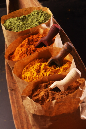 spicy cooking: Assorted ground spices in brown paper bags with small wooden scoops for cooking spicy Asian cuisine, close up high angle view in a receding row