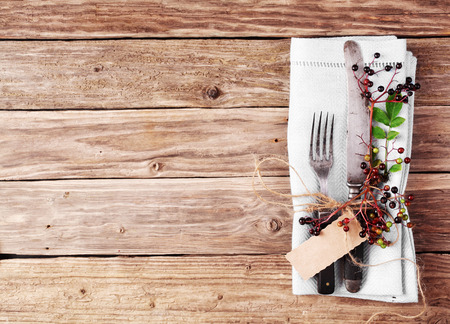 dinner party: Decorative Autumn Table with flatware and napkin on old rustic wooden plate with copyspace Stock Photo