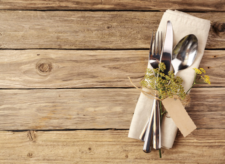High Angle View of Cutlery Tied on White Napkin with Small Leaves on Stem and Empty Brown Tag, Placed on Wooden Table with Copy Space.