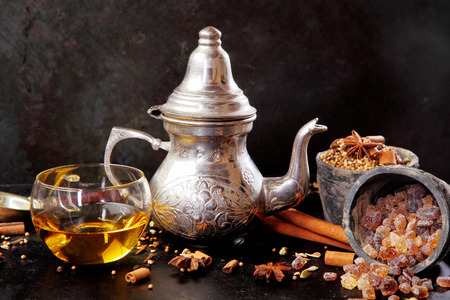 stick of cinnamon: Spicy winter tea in a silver teapot and cup surrounded by aromatic ingredients including stick cinnamon, star anise, and caramelized sugar crystals