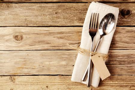 liggande: Hög vinkel tanke på sked och gaffel Bundet på en vit servett med Tom Tag, Placerad på träbord med kopia utrymme.