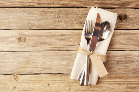 cutleries: Close up Spoon, Fork and Knife Tied on White Napkin with Empty Tag, on Wooden Table with Text Space.
