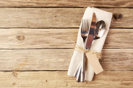 Primer plano Cuchara, Tenedor y cuchillo atado en el blanco Servilleta con etiqueta vacía, en la tabla de madera con el espacio del texto.