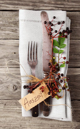 auszeit: Decorative Autumn Table with vintage silverware and napkin on old rustic wooden board with the word Auszeit Stock Photo