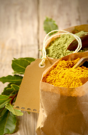 pungent: Brown paper packet of colorful dried turmeric powder, a pungent spice used in curry and Asian and Oriental cuisine, close up view with a blank tag behind over a rustic wood background Stock Photo