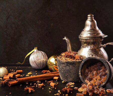 christamas: Preparing festive spicy tea for Christmas with aromatic spices including stick cinnamon , star anise and caramelized sugar with decorative Xmas baubles, a sliver teapot and copyspace Stock Photo