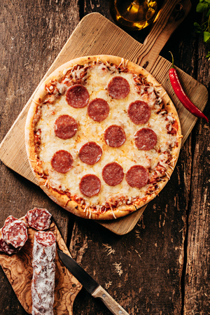 Spicy salami or pepperoni pizza with a red hot cayenne chili being prepared in a rustic kitchen on an old wooden counter, overhead view