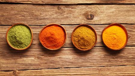 �pices: Rang�e d'�pices color�es dans des bols en vue de dessus sur une table en bois avec le gingembre, la poudre de chili de Cayenne, le curcuma et matcha ou amchoor pour la cuisine asiatique Banque d'images