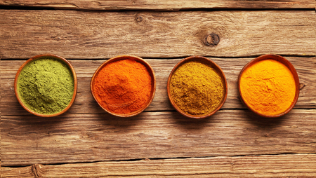 chili powder: Row of colorful spices in bowls viewed from above on a wooden table with ginger, cayenne chili powder, turmeric and matcha or amchoor for Asian cuisine Stock Photo