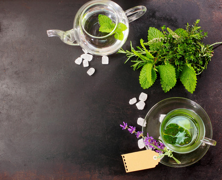 sage: Freshly brewed peppermint tea with fresh herbal ingredients and flowers alongside in a glass cup and teapot for a refreshing healthy drink, overhead view on slate with copyspace