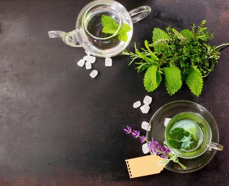 menta: Té de menta recién hecho con ingredientes frescos a base de hierbas y flores junto en un vaso de vidrio y la tetera para una bebida saludable refrescante, vista de arriba en la pizarra con copyspace