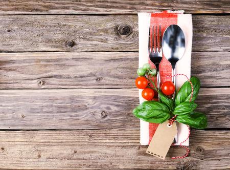 restaurante italiano: Ángulo de visión de alta de Cuchara y Tenedor encima de una servilleta Styled tomates, hojas de albahaca y la etiqueta, Colocado en la tabla de madera con espacio para copiar italiano concepto de restaurante Foto de archivo