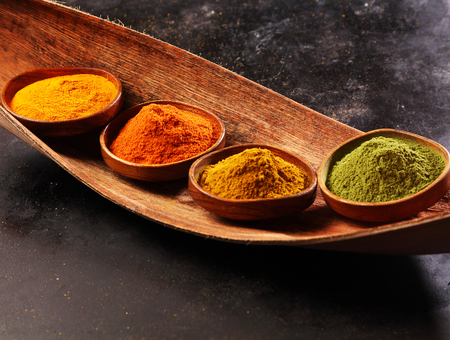 heaped: Four different ground spices heaped in rustic wooden bowls on a wooden salver with amchoor or matcha powder, chili, ginger and turmeric over a dark background Stock Photo