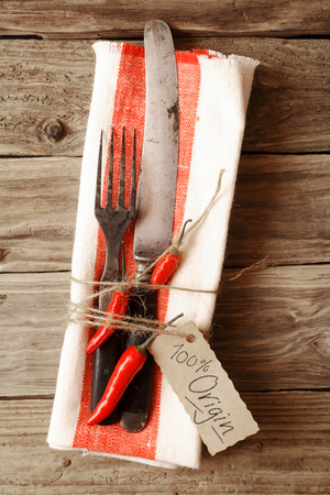 tied down: Close up Fork and Knife Tied on a Napkin with Red Chili Pepper & Tag, Emphasizing 100% origin Message, Placed on Wooden Table.