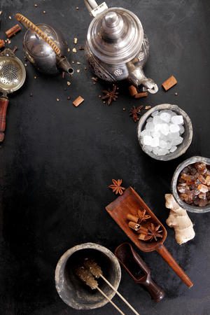 aromatic: Selection of aromatic spices and crystallised sugar for making spicy tea for a winter beverage viewed from above with a teapot and cup of hot tea over black with copyspace