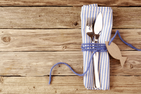 aerial view: Fish Cutlery Tied on a Purple Napkin with Empty Fish Shaped Tag on Top of a Wooden Table with Copy Space.