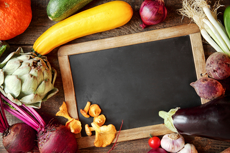 fresh: Fresh fall cooking ingredients including mushrooms, beetroot, artichoke, marrow, peppers onion, pumpkin and spring onion around a blank vintage slate with copyspace for your menu or recipe Stock Photo