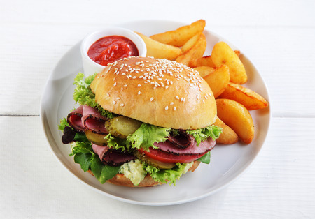 original plate: Roast beef sesame roll with salad trimmings served with French fries or potato wedges and tomato ketchup on a plate, high angle view on a white wooden table Stock Photo