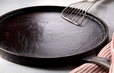 cast iron: Close up Empty Cast Iron Burger Skillet with Spatula on Top of a Table at the Kitchen. Stock Photo
