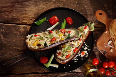Top down view of a stuffed aubergine with couscous or quinoa on a brown vintage wooden background