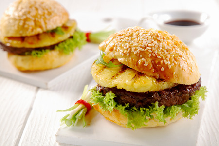 Close up Gourmet Hawaiian Burgers with Patties, Pineapples and Veggies, Served on a White Table.