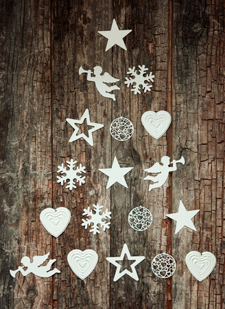 outs: Decorative Christmas tree design of individual white seasonal cut outs of angles, hearts snowflakes and baubles arranged as a tree on a rustic wood background