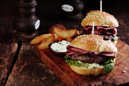 Gastronomische Smakelijk Steak Burgers met Ham Slices op een houten dienblad met Aardappel Wiggen en dipsaus.