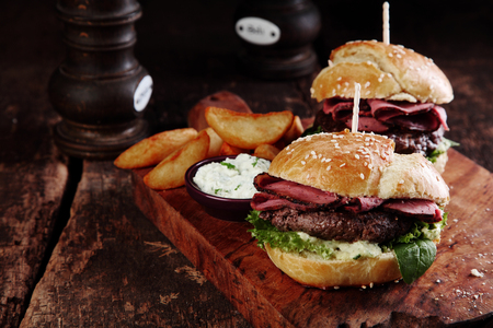 wedges: Gourmet Tasty Steak Burgers with Ham Slices on a Wooden Tray with Potato Wedges and Dipping Sauce.