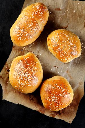 bollos: Vista superior de cuatro sabrosa hamburguesa bollos, rociado con semillas de sésamo, en la cima de un Libro Sobre Fondo Negro. Foto de archivo
