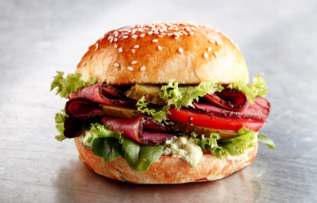 street food: Delicious sesame bun with sliced roast beef or pastrami with lettuce, tomato, gherkin, and mayo on a silver counter in a cafeteria or restaurant