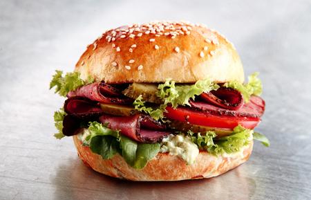 Heerlijke sesam broodje met gesneden rosbief of pastrami met sla, tomaat, augurk, en mayo op een zilveren teller in een cafetaria of restaurant