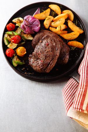 carne de res: Ángulo de visión de alta de Sabroso Beef Steak asado con verduras a la parrilla en sartén de hierro fundido, que se sirve en la mesa para la cena.