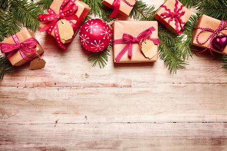 adviento: Frontera festiva de Navidad con regalos atados con cinta roja, a juego con bolas rojas y frescas de pino follaje sobre la madera r�stica con copyspace para su felicitaci�n navide�a Foto de archivo